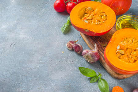 Autumn food cooking concept. Pumpkin cooking background, with half sliced pumpkin, olive oil and spices top view copy space