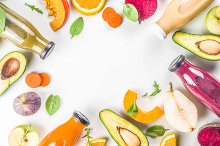 Fruit and vegetable smoothie concept. Portioned bottles with fruit and vegetable smoothies flatlay with fresh ingredients on white table background