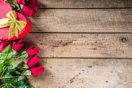 Valentine's day congratulations concept. Background for congratulation cards. Roses, valentine gift box with bow, cup of hot chocolate or coffee, notepad. On a wooden background, top view copy space