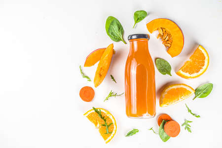 Orange healthy smoothie bottles with ingredients. Vegetable smoothie or juice with carrot, pumpkin, oranges, white table background, flatlay copy space Reklamní fotografie