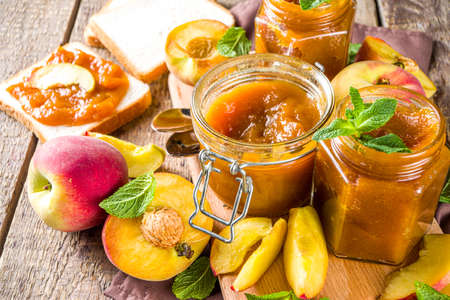 Homemade peach jam in different jars, with fresh organic peaches on wooden rustic background copy space Reklamní fotografie