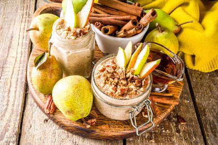 Sweet and spicy autumn breakfast oats recipe, Homemade pear and cinnamon overnight oatmeal with spices and yogurt, wooden background copy space Stock fotó