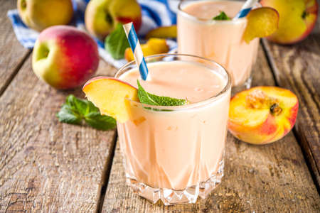 Summer breakfast drink, fresh blended peach smoothie, peach yogurt with nectarine fruit slices, rustic wooden background copy space