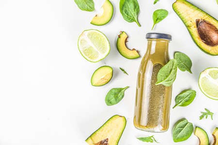 Green healthy smoothie bottles with ingredients. Vegetable smoothie or juice with baby spinach, avocado and lime, white table background, flatlay copy space