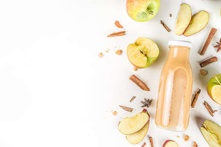 Apple and pear smoothie in small portioned bottle, with fresh autumn traditional spices, flatlay on white background Stock fotó