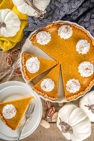 Traditional Autumn Pumpkin Pie. Homemade American Pumpkin pie topped with Whipped Cream. Rustic wooden table bakcground with Cozy plaid and sweater.
