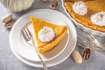 Traditional Autumn Pumpkin Pie. Homemade American Pumpkin pie topped with Whipped Cream.