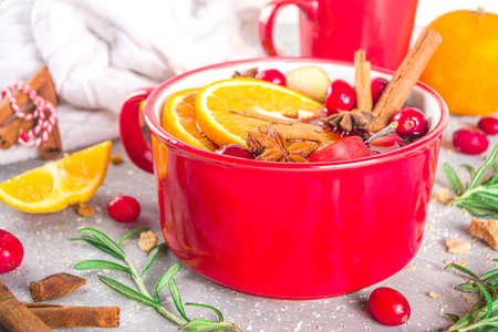 Mulled Wine Hot Drink with Citrus and Spices, Traditional Autumn Winter Warm Alcohol Beverage, in small portioned red stewpan or mug with Mulled Wine Ingredients - fruit and spices, copy space