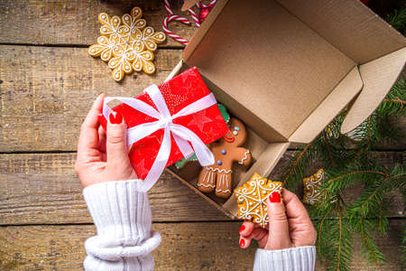 Christmas Gift Box package. Gift exchange Christmas New Year concept on covid-19 pandemic. Secret Santa post game. Packing gifts, cookies in parcel. Wooden background, with Xmas tree branch and decor