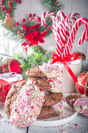Homemade chocolate cracked brownie cookies dipped in white chocolate and candy cane bits. Idea recipe for Christmas party treats, winter holiday food