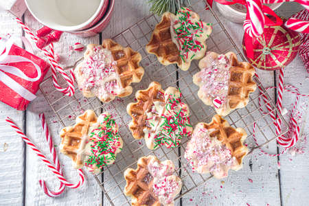 Stack of homemade Belgian waffles for Christmas breakfast. Traditional waffles dipped in white chocolate, with Candy Cane crumbs and festive sugar sprinkles 版權商用圖片