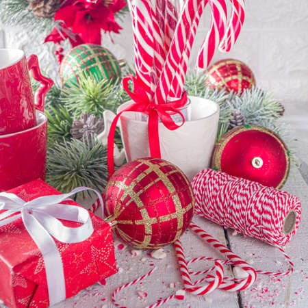 Festive composition with fir tree branches, Christmas decor and baubles, gift box with festive ribbons, Xmas sweets and mugs for hot chocolate, white background copy space