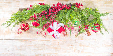 Festive Xmas background with fir tree branches, red winter berries, candy cane decoration and festive gift boxes, top view copy space