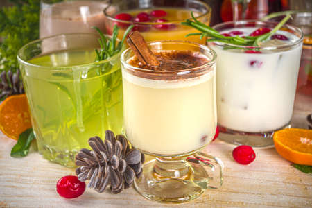 Set of different Christmas and winter drinks. An assortment of Christmas cocktails, hot and cold beverages, in cozy wooden home background with Xmas decor