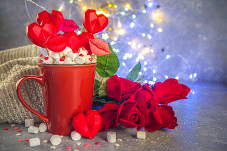 Valentine`s day sweets concept, festive holiday background with hot chocolate red cup and set of red hearts sweets on sticks in cup, with red roses and bokeh lights effect