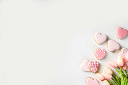 Homemade pick sugar glazed Valentine day cookies. Valentine heart shaped bakings. White stone background copy space top view Stock Photo