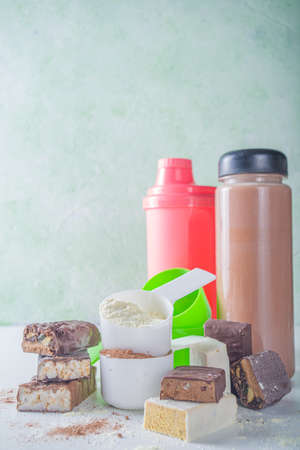 Healthy fit and sport background. Slimming concept. Variety of flavors of protein cocktail powder, ready-made cocktail in bottle and bars on white background.