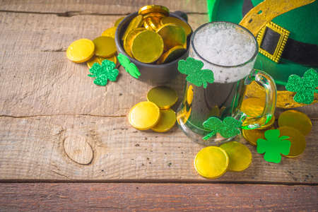 St Patrick's Day Pub Bar menu background. Green Beer In Glass with And with horseshoe, shamrock clover decor, gold coins, on green bokeh glittering background. St Patrick's holiday greeting card mock up