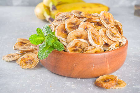 Homemade dried banana, organic banana chips in wooden bowl, on gray concrete table background with fresh yellow bananas copy space