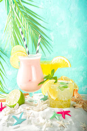 Summer tropical sea holiday vacation concept. Three various glass with summer cold cocktail drinks, on sand with seashells and starfish, light blue wooden background