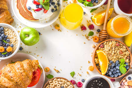 Various breakfast food concept. Traditional healthy breakfast foods and drinks - oats, granola, yoghurt, smoothie bowl, toasts, cereal, growing, coffee and tea cup, orange juice, with fruit, berry