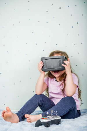 Kids Gaming video games concept. Toddler or young girl, playing game with joystick, smart-phone, VR glasses and headphones, enjoying games, sitting on sofa in living room at home.