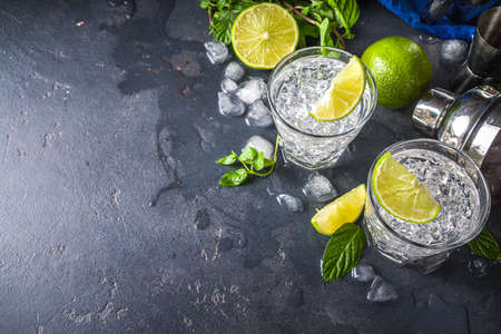 Summer paloma cocktail, vodka lime, mojito or gin tonic with lime wedge and crushed ice in rocks, two cold alcohol beverage glasses on black background copy space