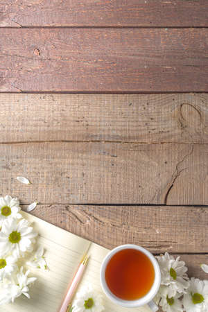 Cozy breakfast in spring or early autumn tea with bouquet of Chamomile daisy flowers and note book. Copy space, top view flat lay