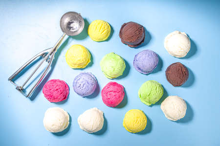 Colorful various ice cream scoops pattern on pastel blue background. Summer minimalism pattern flat lay with hard light. Chocolate vanilla blueberry strawberry pistachio orange ice-cream balls top view