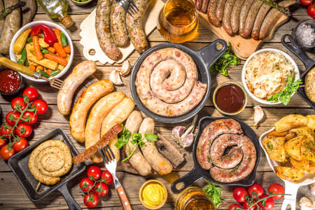 Assortment of different fried sausages. Set with various meat Bavarian, Frankfurt, German grilled sausages, Oktoberfest or summer BBQ party concept, old wooden table background copy space top view