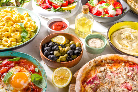 Set of different Mediterranean foods: olives, mozzarella tomato salad, Greek salad, pasta, tortellini ravioli, pizza, pita sandwich, shish kebab, shakshuka, hummus, top view