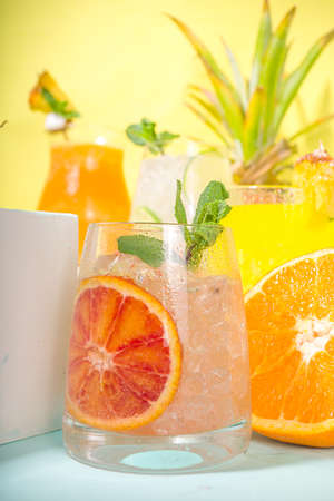Colorful summer drinks set. Various bright alcohol cocktails and beverages, in different glasses, with tropical fruit on modern bright background copy space