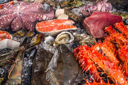 Set of various fresh raw seafood - octopus, crab, squid, shrimp prawn, oyster, mussels, salmon tuna dorada fish with spices of herbs lemon, black background with crushed ice copy space top view Standard-Bild