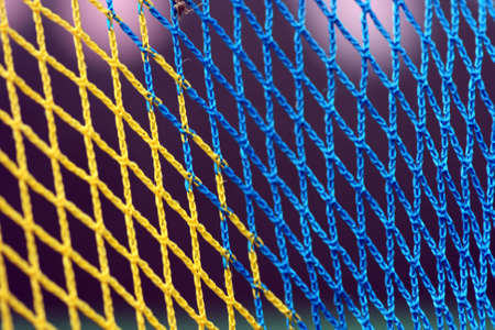 A closeup on a basketball net in blue and yellow Stock Photo