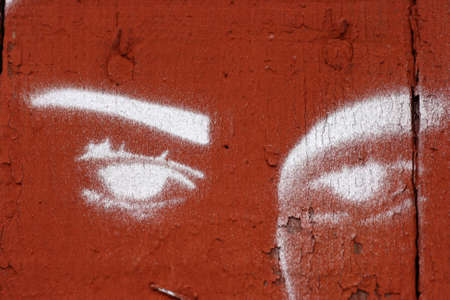 Graffiti painting of eyes on red wood
