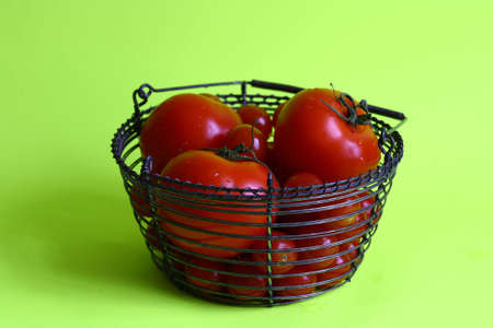 A metallwiring bowl filled with tomatoes in different sizes
