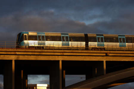 A subway train on a bridge with good sunshine and dark cloudy background
