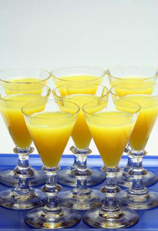 Orange juice in old glasses on a blue tray