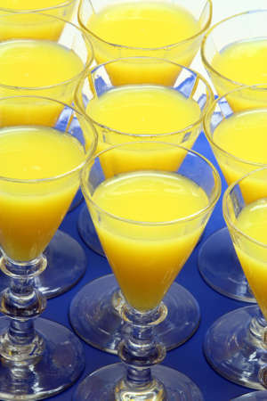 Closeup on orange juice in old glasses on a blue tray Stock Photo