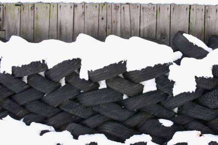 A lot of  tyres against a barn wall
