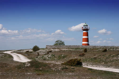 A lighthouse in white and red with a nice blue summer sky Stock Photo