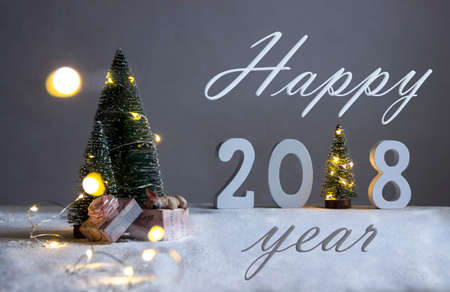 on a snow-covered field under the fir-trees, the dog is sleeping on gifts and in the distance are the figures 2018 where in the role of a Christmas tree with lights card happy 2018 year