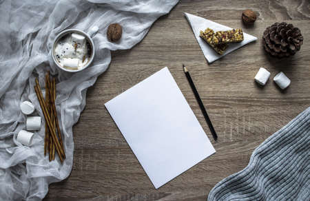 on a wooden background a white sheet and a hand write in black pencil on paper, and on the left a marshmallow and sweet straw strips, cloth, walnuts, a cone, a muesli bar on a white triangular napkin, a mug with cocoa, in which lies a melted snowman from marshmallows Stock Photo