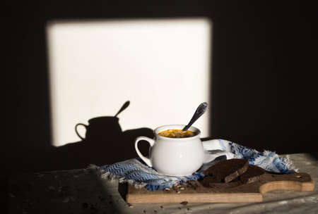 on the table blue napkin with ornament pattern and soup tureen with yellow soup on the sun bread wooden board seeds dark background