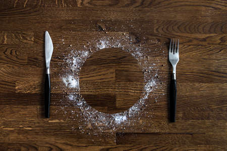 on a wooden background of small dark brown discs circle dish sea salt pepper seasoning coriander poured knife fork