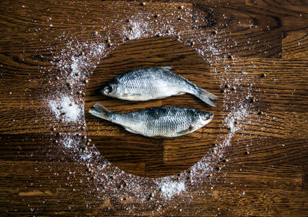 on a wooden background of small dark brown discs circle plate sea salt pepper seasoning coriander padded in the center of a couple two fish dried salted