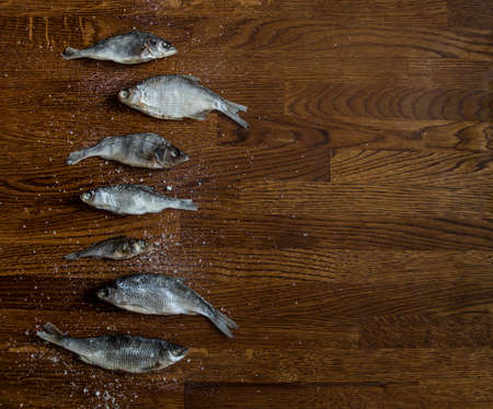 on a wooden background of small dark brown on the side lie salted dried fish large salt Фото со стока