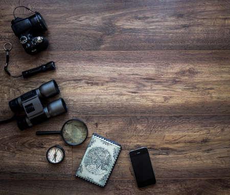 on a dark wooden background passport camera magnifier lantern compass binoculars phone smartphone mobile journey vacation
