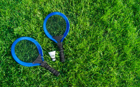 on the green grass lawn lie two blue racquets and a white cape