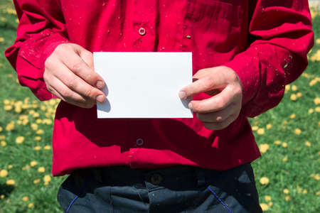 male working hands in a working shirt red burgundy color and pants dark blue holding a white sheet of paper ad rally strike copy space